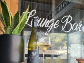 A bottle and glass of Basalt Rieslingon a tall bar table facing the lounge bar.