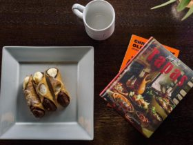 Aerial photo of square plate with cream-filled cannolis, an empty white coffee mug and books