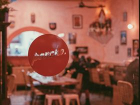 Window with round red pancho decal with restaurant tables behind