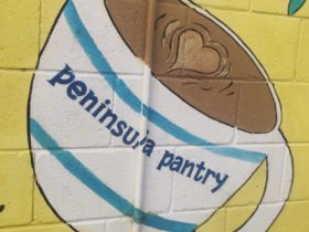 Mural of a coffee cup with Peninsula Pantry written on it