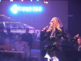person in drag singing to audience with neon sign hanging on wall in distance