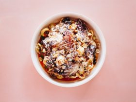 Aerial shot of bowl of orecchiette, duck ragu, radicchio, hazelnuts, salata on pink background
