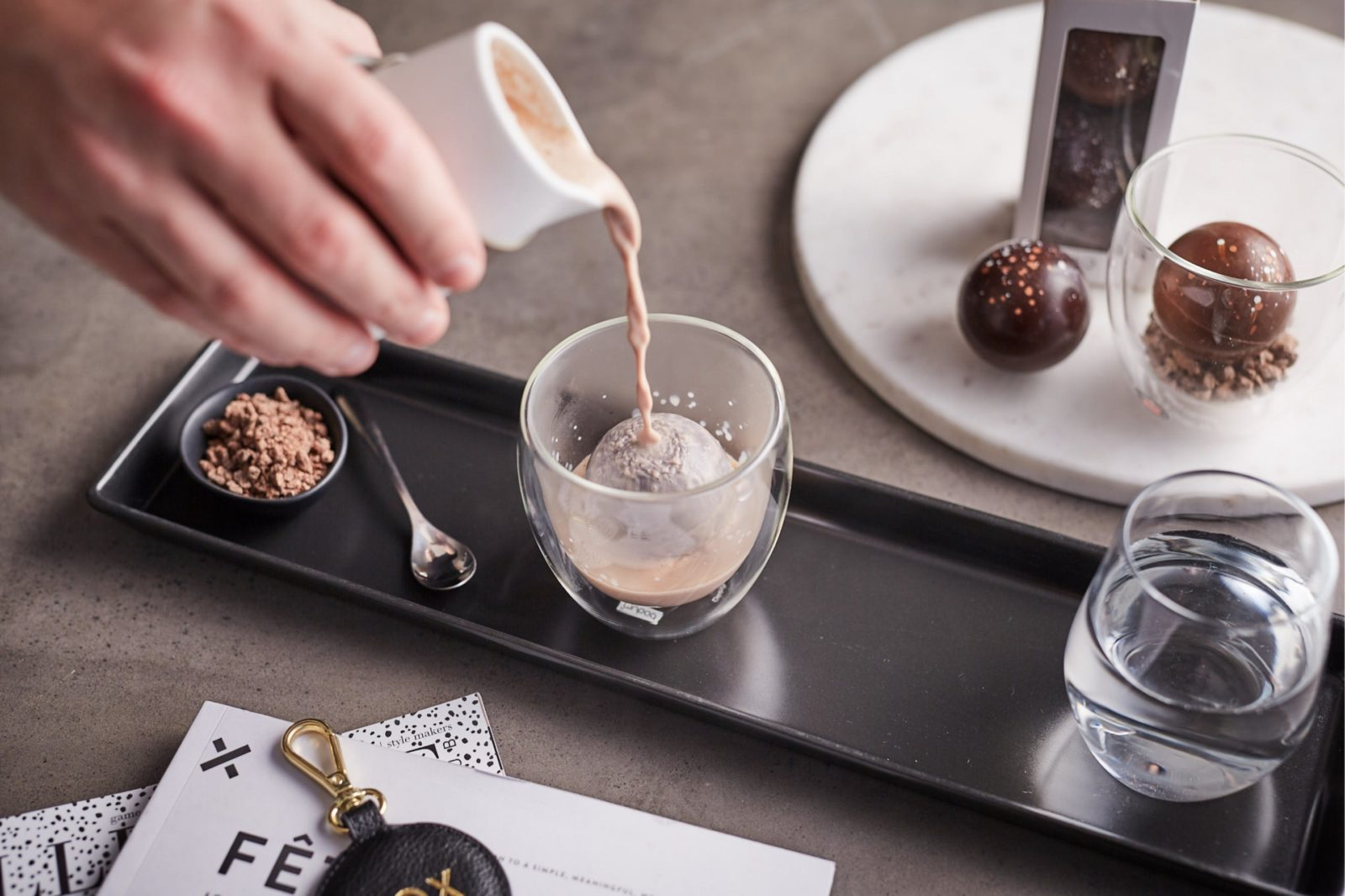Pour the hot chocolate mix over the sphere, as it melts away our handmade marshmallow is revealed.