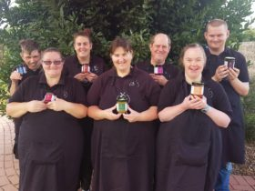 Group of people in aprons posing while holding jars of produce