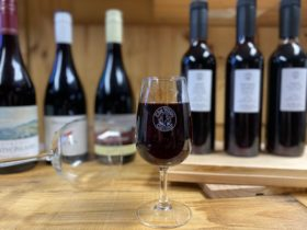 Red Wine Glass in Focus With full bottles and half size tasting backs behind