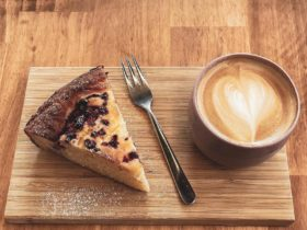 slice of cake and mug of coffee in ceramic cup on rectangle wooden platter