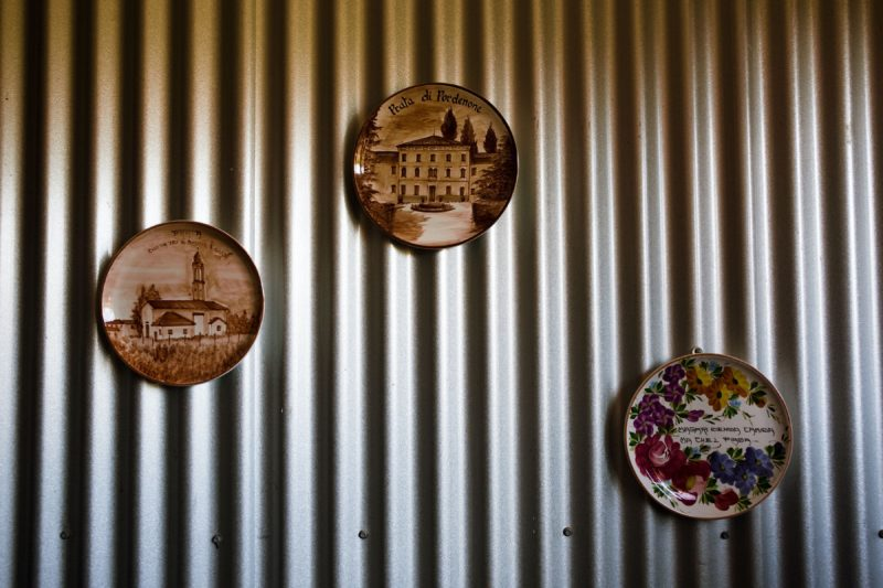 Three northern Italian plates on the corrugated iron wall of the Cellar Door highlight heritage