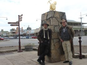 Dan and Ian standing leaning against granite cann, dressed in long coats and hats
