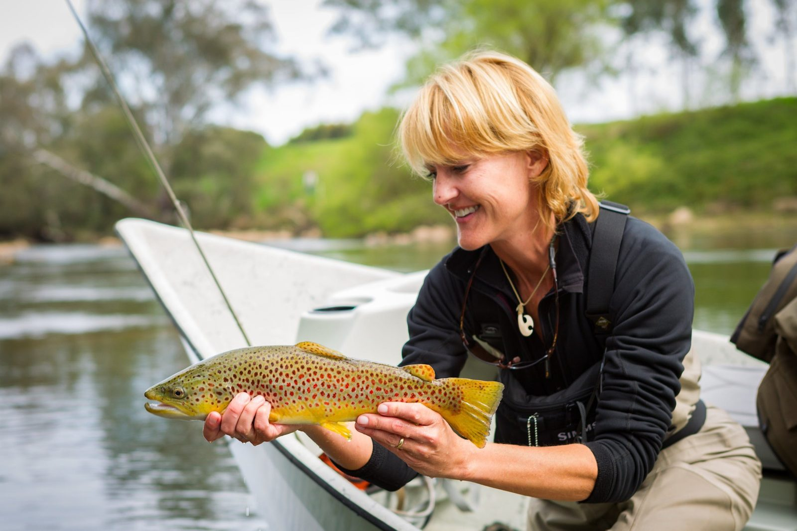 Lady gently cradling a brown trout just prior to release