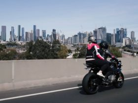 Rider and pillion on black BMW motorcycle riding over bridge looking towards a city skyline