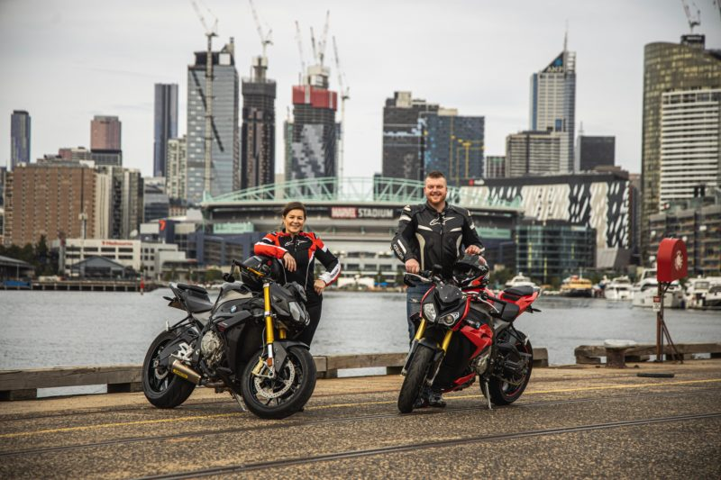 Female and male standing next to their BMW motorcycles in front of a bay dock