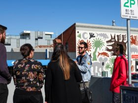 Tour group stand in front of large scale mural and have a discussion.