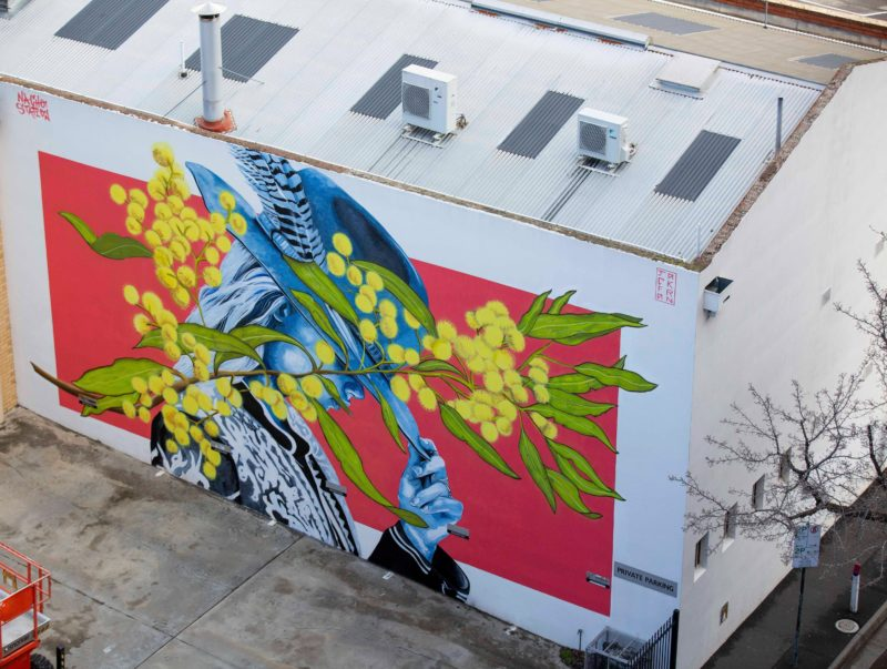 Arial view of a large scale mural depicting a woman tilting her hat down to the sun.